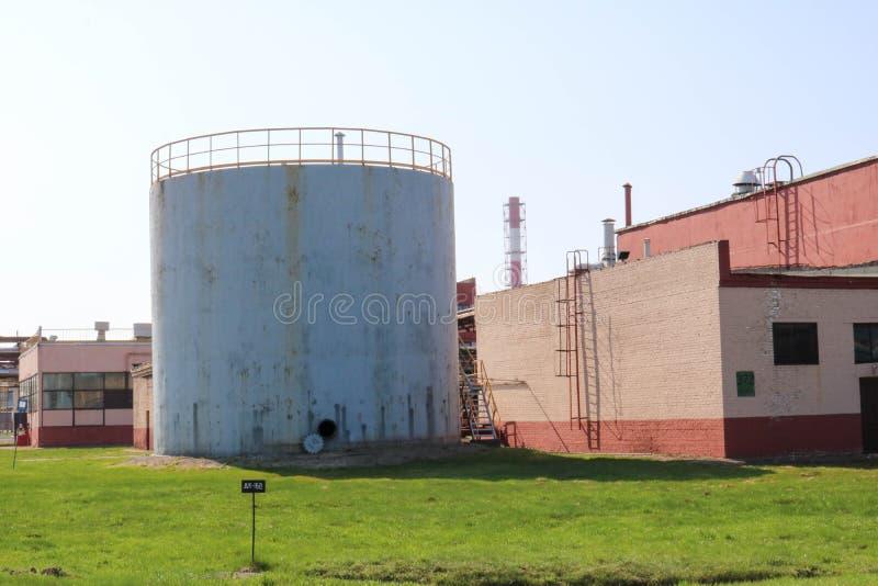 Un envase gris grande con una portilla abierta y edificios de la producción en una refinería de petróleo, producto petroquímico,  fotografía de archivo libre de regalías