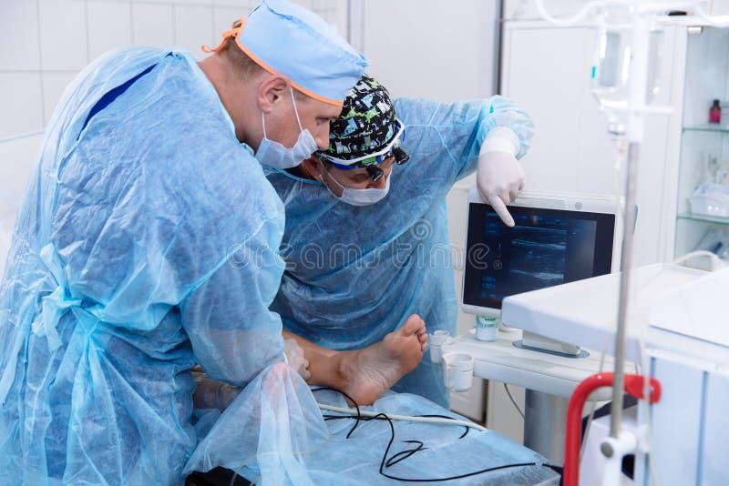 Un equipo de doctores en vestidos médicos estéril realiza cirugía en un cuarto quirúrgico El cirujano muestra el diagnóstico fotografía de archivo libre de regalías