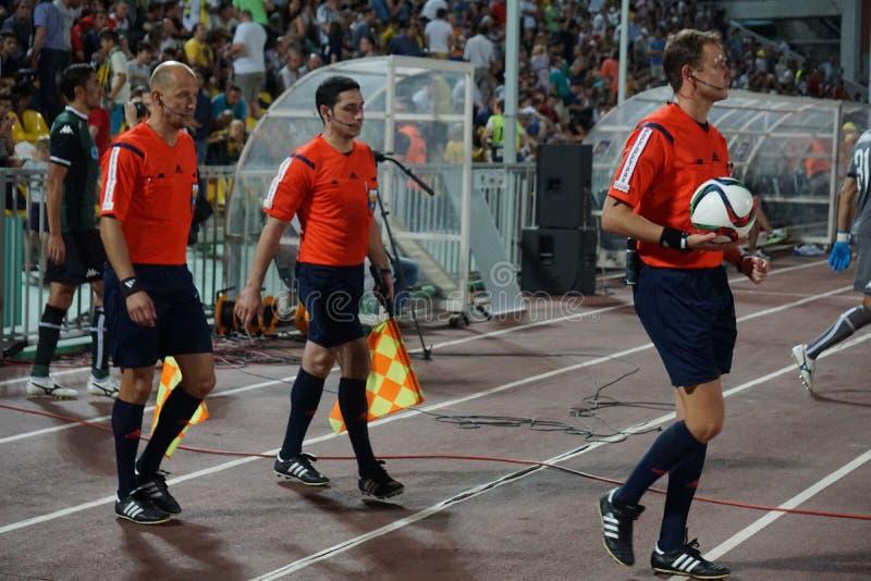 Un equipo de fútbol arbitra hacia fuera en el campo antes del partido fotografía de archivo