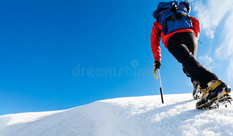 Un escalador alcanza el top de una montaña nevosa Concepto: valor, éxito, perseverencia, esfuerzo, uno mismo-realización fotos de archivo