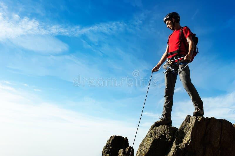Un escalador ayuda a su socio a alcanzar la cumbre de un PE de la montaña imagen de archivo