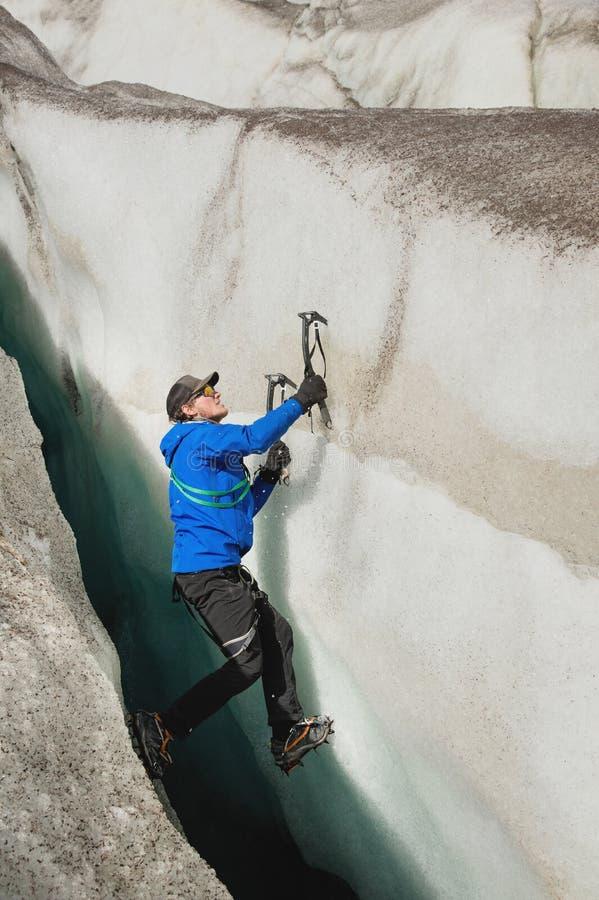 Un escalador libre sin seguro con dos hachas de hielo sube de una grieta en el glaciar El subir libre sin cuerdas fotografía de archivo libre de regalías