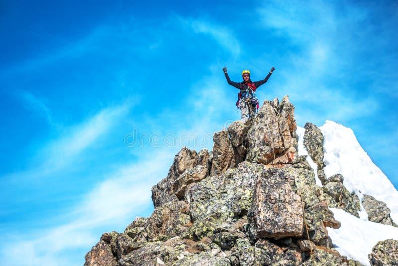 Un escalador que alcanza la cumbre fotos de archivo