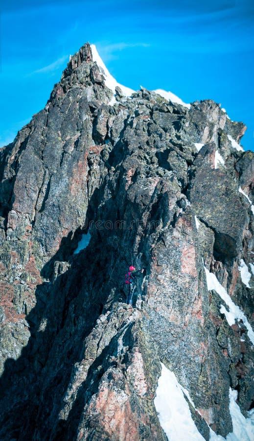 Un escalador que alcanza la cumbre de la montaña fotografía de archivo