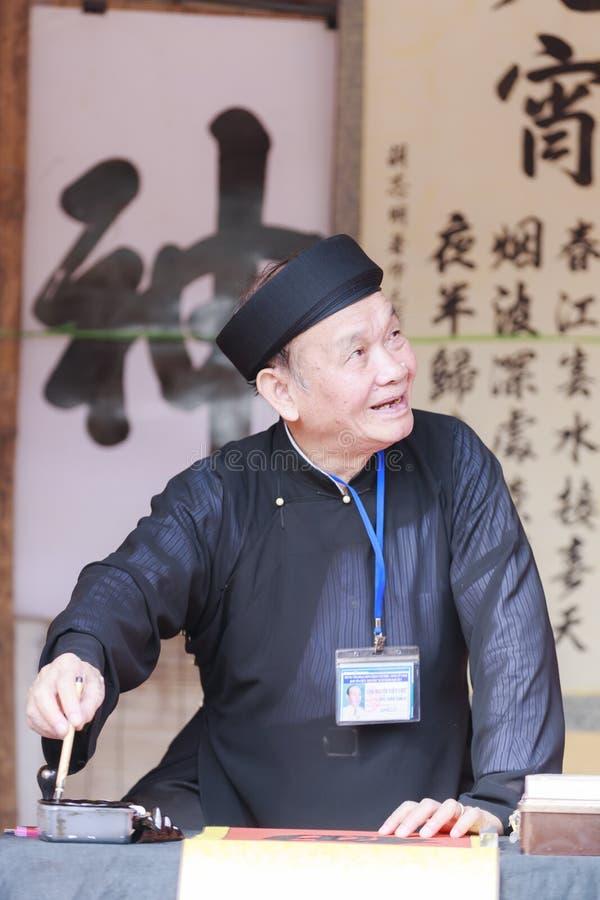 Un escolar escribe caracteres chinos de la caligrafía en el templo de la literatura imágenes de archivo libres de regalías