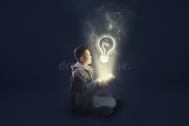 Un escolar que lleva una tenencia y una lectura de la chaqueta un libro mágico con la luz mística que sale Ideas de la lectura Re imagen de archivo libre de regalías
