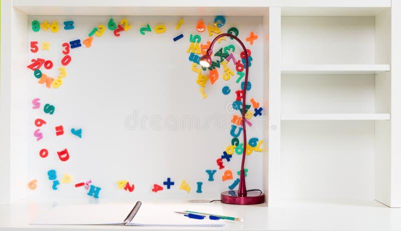 Un escritorio de la escuela del ` s del niño con un cuaderno del papel cuadriculado, pluma y lápiz y un fondo blanco con las letr fotos de archivo
