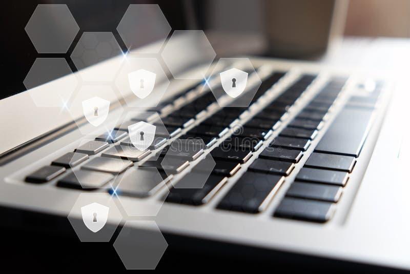 Un escudo y un ojo de la cerradura en pantalla virtual hexagonal en fondo del teclado fotografía de archivo libre de regalías