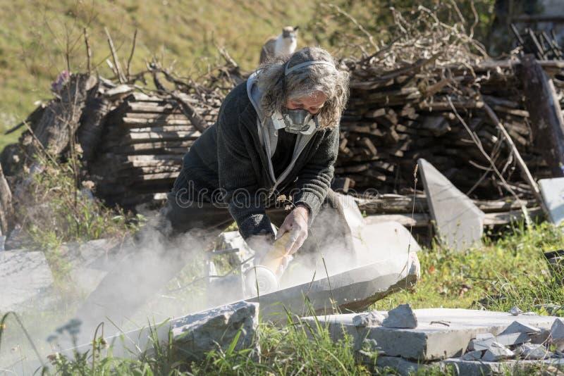 Un escultor que trabaja fuera de llevar la máscara protectora fotografía de archivo libre de regalías
