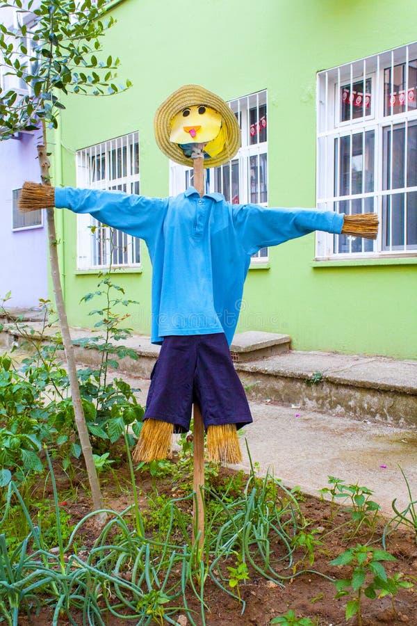 Un espantapájaros en un jardín de la escuela foto de archivo