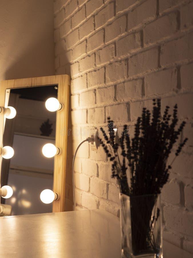 Un espejo del maquillaje con las bombillas en un fondo de la pared de ladrillo Luz caliente Lavanda foto de archivo
