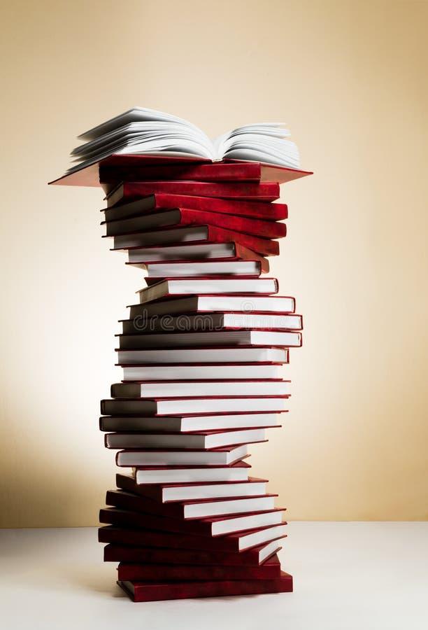 Un espiral de pilas de libros bajo la forma de DNA y libro de texto abierto en el top imágenes de archivo libres de regalías