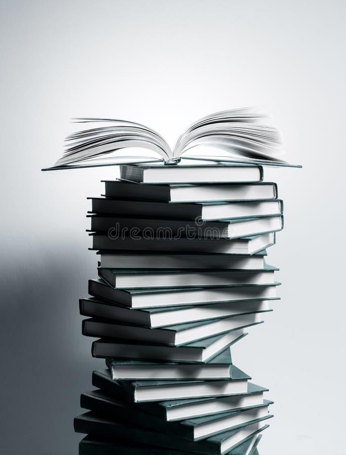 Un espiral de pilas de libros bajo la forma de DNA y libro de texto abierto en el top imagen de archivo libre de regalías