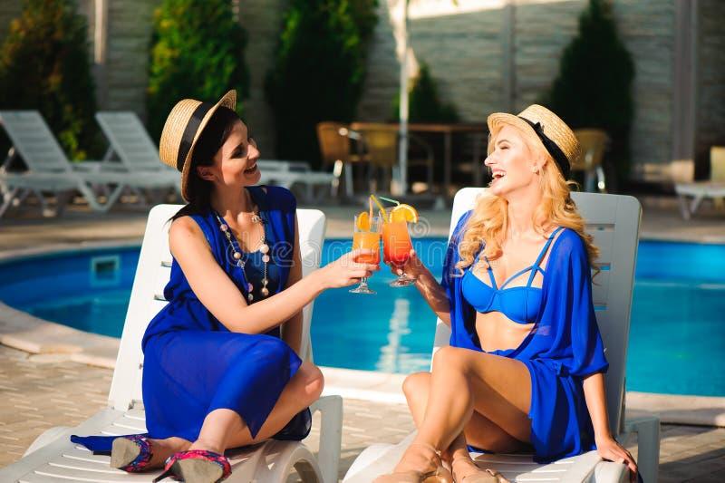 Un'esposizione al sole felice di due ragazze vicino allo stagno sulle sedie di spiaggia immagini stock libere da diritti