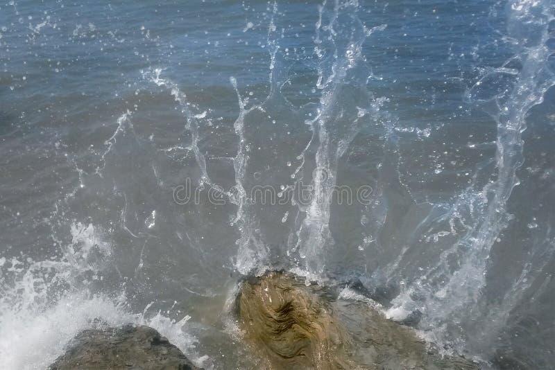 Un espray de la espuma del mar blanco está batiendo contra las piedras foto de archivo