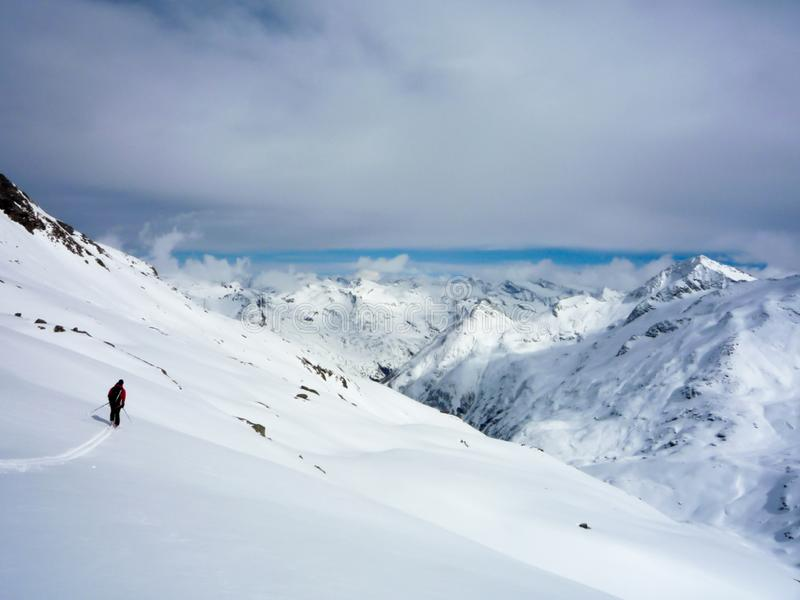 Un esquiador backcountry que esquía abajo de un alto glaciar alpino en las montañas austríacas en invierno fotos de archivo libres de regalías