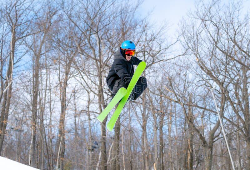 Un esquiador realiza un gancho agarrador del mediados de-aire en un parque del terreno imagen de archivo