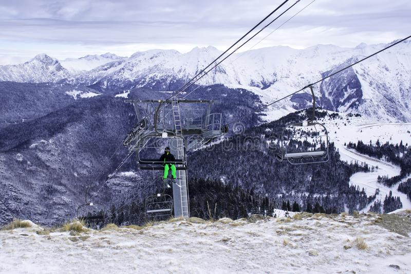 Un esquiador solitario sube las montañas en un teleférico para la pendiente imagen de archivo libre de regalías