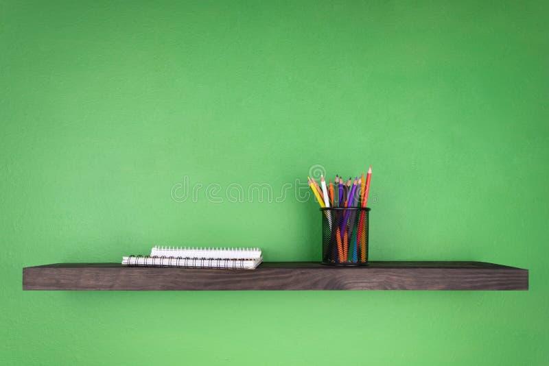 Un estante de madera oscuro contra la perspectiva de una pared verde en cuál se fija un vidrio con los lápices y los cuadernos co fotografía de archivo