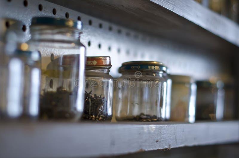 Un estante de tarros y de tornillos foto de archivo