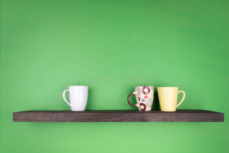 Un estante del color oscuro con texturizar la madera está instalado en una pared verde; hay tres diversas tazas del color en el e fotos de archivo libres de regalías