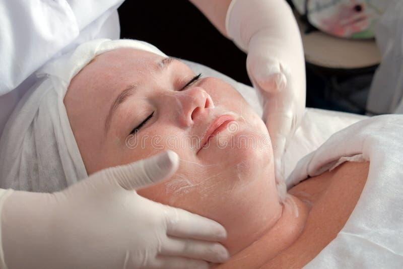 Un esthéticien professionnel employant une solution de savon lave le visage d'une femme La procédure de nettoyer la peau sur le c photo stock