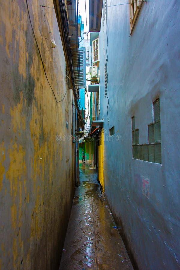 Un estrecho, un callejón colorido, oscuro entre dos edificios con las ventanas abiertas y obturadores foto de archivo