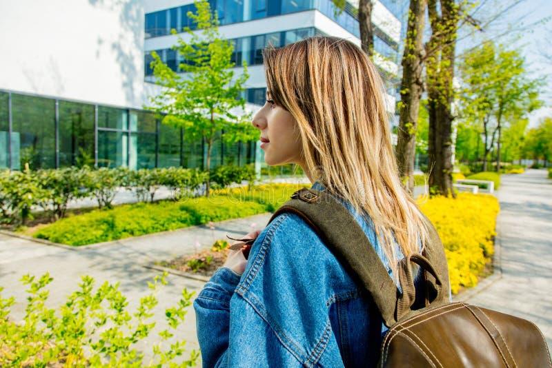 Un estudiante joven con una mochila está la primera vez cerca de campus foto de archivo