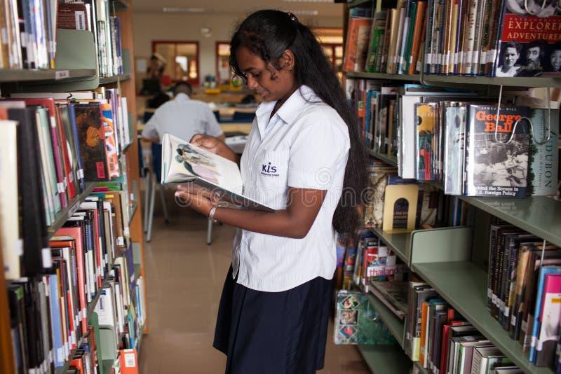 Un estudiante joven lee un libro en la biblioteca de universidad foto de archivo libre de regalías
