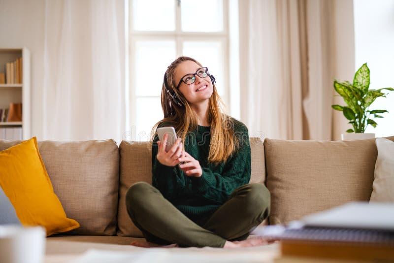 Un estudiante joven que se sienta en la tabla, usando los auriculares al estudiar foto de archivo