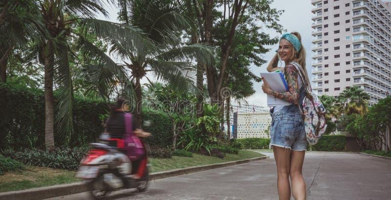 Un estudiante universitario hermoso va a la escuela temprano por la mañana en un buen humor Imagen soñadora de una muchacha moder imágenes de archivo libres de regalías