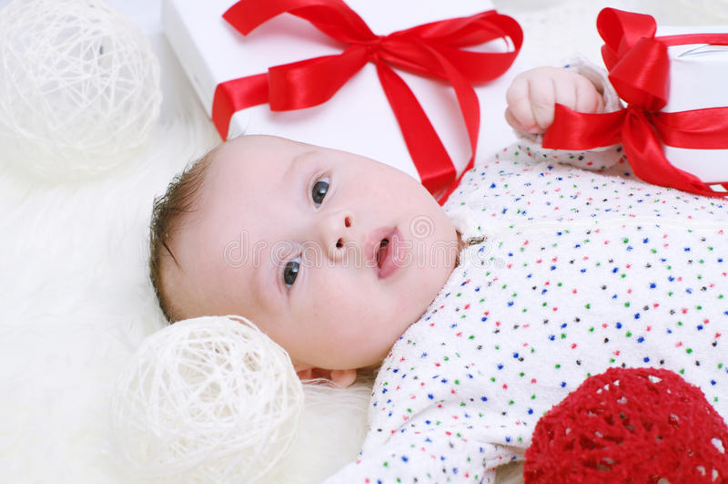 Un'età del bambino di 3 mesi che si trovano fra i regali fotografie stock libere da diritti