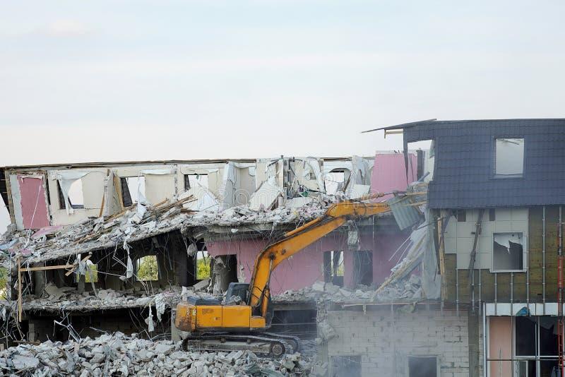 Un excavador amarillo demuele un edificio de varios pisos con una cucharón La casa destruida, pisos quebrados, destruyó las pared fotos de archivo libres de regalías