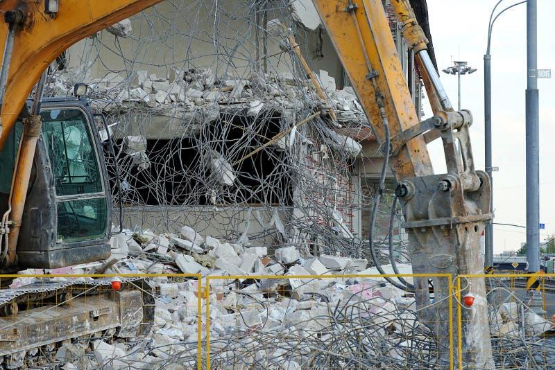Un excavador demuele un edificio de varios pisos con una herramienta del cincel La técnica destruye el edificio, accesorios colga imágenes de archivo libres de regalías