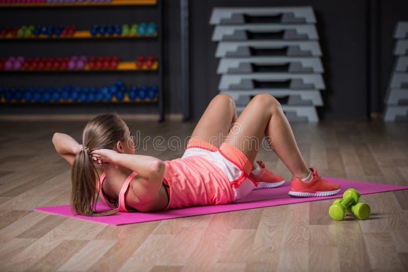 Un exersice di pratica di sport della donna graziosa su un fondo della palestra Una bella ragazza sta oscillando la stampa in una immagine stock libera da diritti