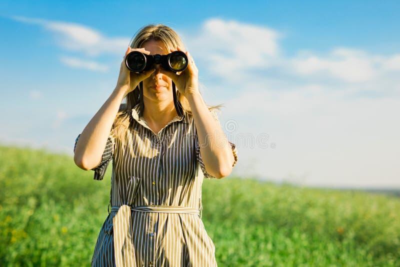 Un explorador de la mujer está utilizando los prismáticos negros - al aire libre imagen de archivo libre de regalías