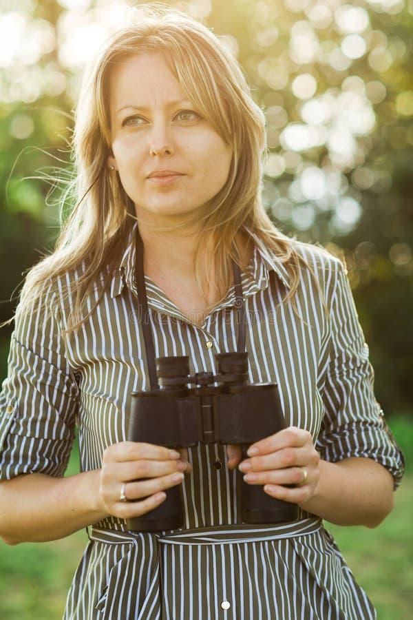 Un explorador turístico de sexo femenino con los prismáticos permanece al aire libre imágenes de archivo libres de regalías