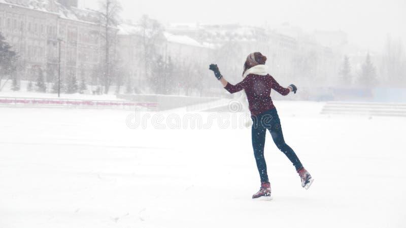 Un exterior sonriente joven del patinaje de hielo de la mujer Nevadas pesadas imagen de archivo