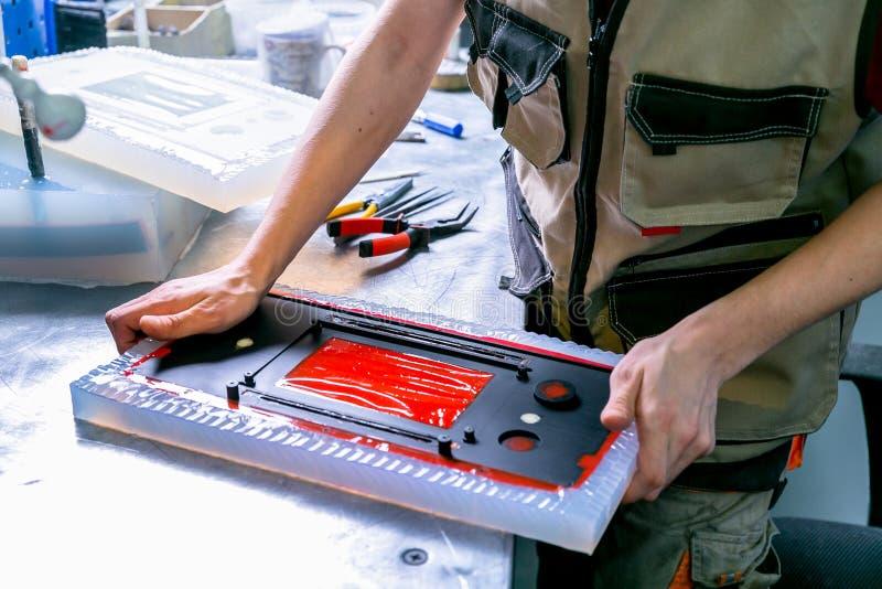 Un extrait de travailleur le d?tail en plastique du moule Fabrication des produits en plastique Concept moyen d'affaires Remet le photographie stock libre de droits