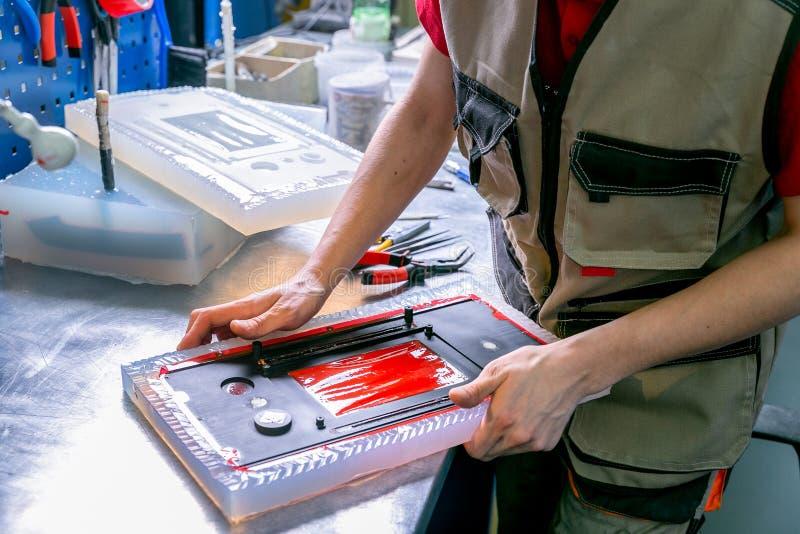 Un extrait de travailleur le d?tail en plastique du moule Fabrication des produits en plastique Concept moyen d'affaires Remet le images libres de droits