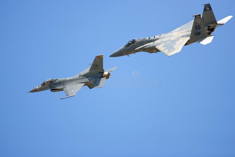 Un F-15 e un F-16 fanno un flyby fotografia stock libera da diritti
