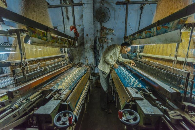 Un fabricant en soie examine son travail à une petite usine à Varanasi, Inde