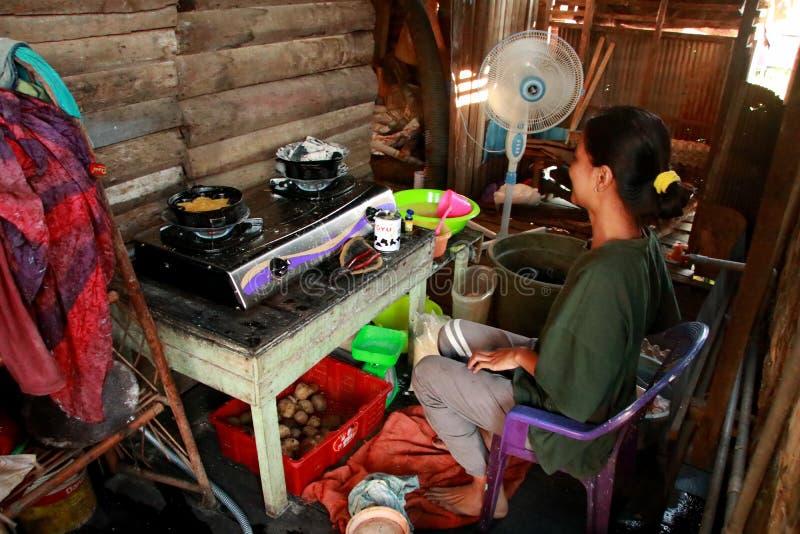 Un fabricante del sur t?pico de la torta de Kalimantan Bingka en Banjarmasin al cocinar foto de archivo