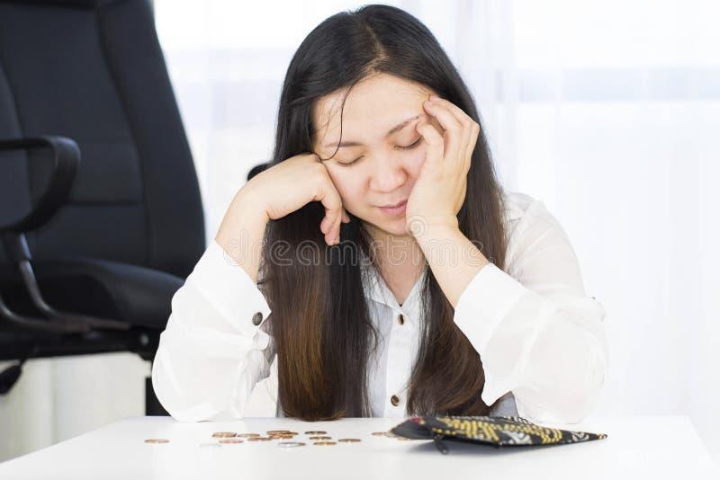 Un fallimento, si è rotto e la donna frustrata sta avendo problemi finanziari con le monete lasciate sulla tavola e su un portafo fotografia stock
