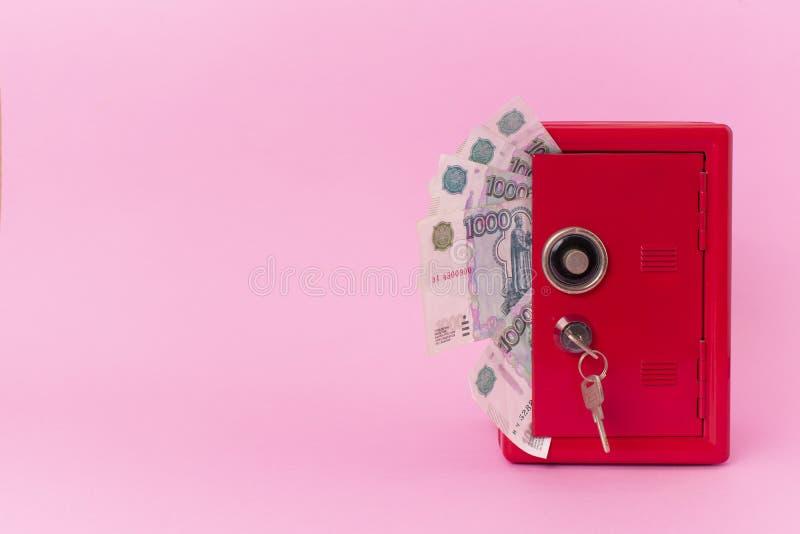 Un fan di soldi russi dentro la cassaforte rossa su fondo rosa banca con la chiave fotografia stock