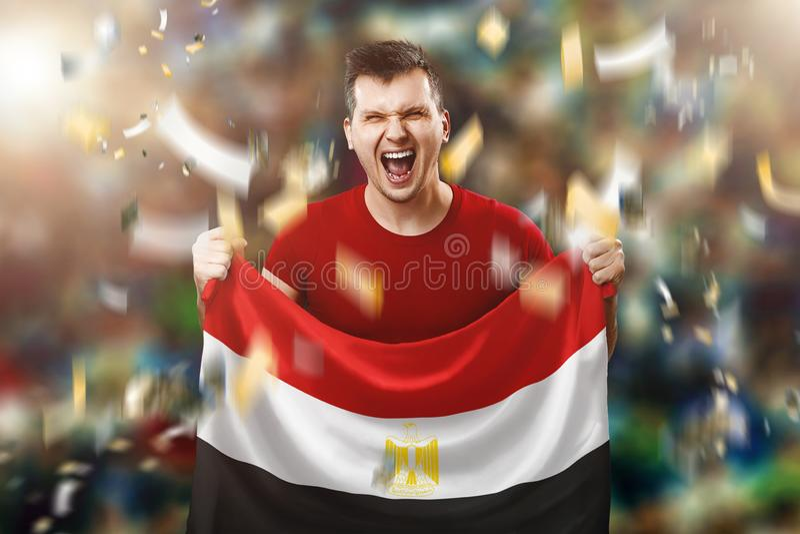 Un fan egiziano, un fan di un uomo che tiene la bandiera nazionale dell'Egitto in sue mani Fan di calcio nello stadio Media misti fotografie stock libere da diritti