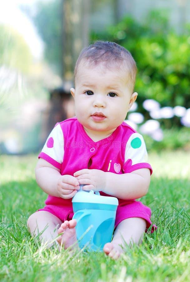 Un fare da baby-sitter grazioso sull'erba che tiene una bottiglia immagini stock libere da diritti