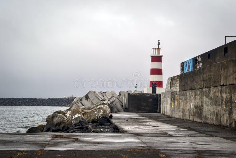 Un faro blanco rojo en un embarcadero de piedra en un puerto en la isla de Pico foto de archivo libre de regalías