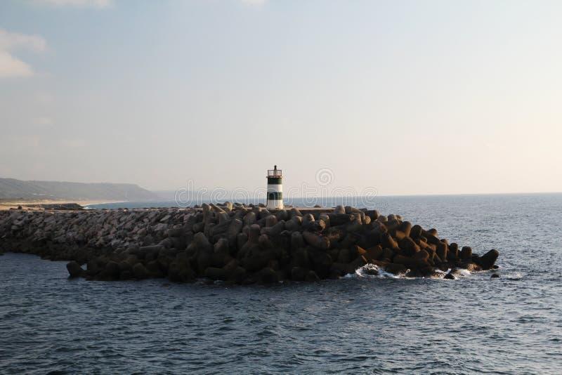 Un faro en la playa de Océano Atlántico en Nazare, Portugal fotografía de archivo