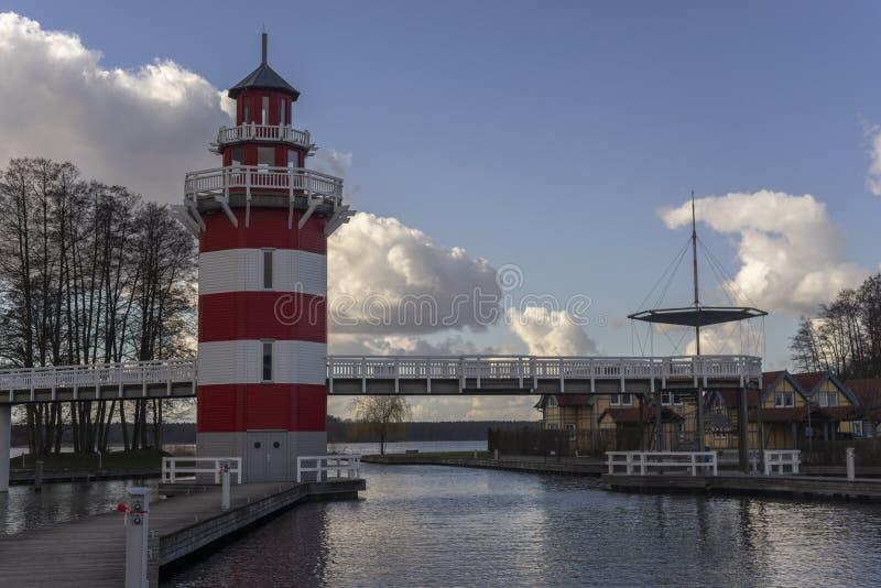 Un faro a strisce rosso e bianco su un piccolo porto con i cottage di estate in Germania vicino il lago fotografia stock libera da diritti